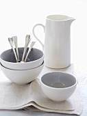 Porcelain bowls, jug and spoons on fabric napkin