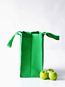 Three Granny Smith apples with a green shopping bag