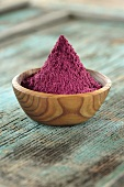 Acai powder (diet aid) in small wooden bowl