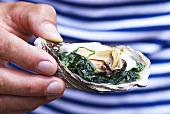 An oyster with spinach and cream
