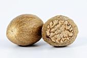 Whole nutmeg and half of a nutmeg