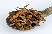 Dried lily buds on wooden spoon