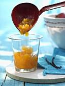 Ladling peach and mango jam into jar