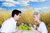 Young couple eating salad in a cornfield