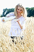 Blond woman with milk and cornflakes in a cornfield