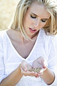 Blond woman holding cereal grains in her hands