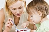 Little girl having breakfast with her mother