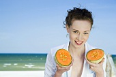 Young woman on beach with Charentais melon