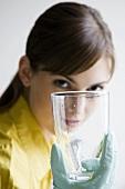 Young woman washing a glass