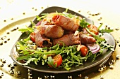 Bacon-wrapped prunes with rocket, tomatoes and pine nuts