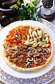 A round pizza with four different toppings
