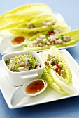 Pork with spring onions on lettuce leaves, chilli sauce