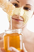 Woman with honey facial mask, jar of honey and honeycomb