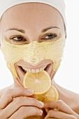 Woman with honey facial mask eating lemon