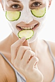 Young woman with cucumber facial mask