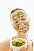 Young woman with herbal face mask