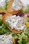 Cheese spread on toast on salad leaves (close-up)