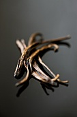 Vanilla pods on reflective surface