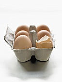 Brown eggs and an eggshell in an egg box