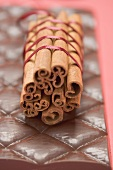 Cinnamon sticks, tied together with red ribbon, on chocolate