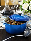 Beef ragout in pot with red wine
