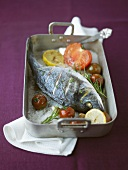 Sea bream baked on sea salt with tomatoes and rosemary