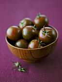Schwarze Tomaten in einer Holzschüssel
