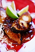Fish in caramel sauce with rice and lime wedges