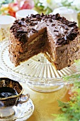 Rum chocolate cake, a piece removed, on cake stand