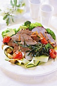 Sliced roast veal on a bed of vegetables