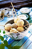 Fish dumplings on wooden skewers