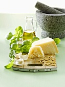 Ingredients for pesto on chopping board, mortar and pestle