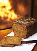 Rye bread, partly sliced, in front of open fire