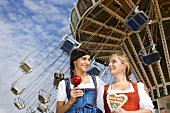 Women in dirndls with toffee apple & Lebkuchen heart (Oktoberfest)