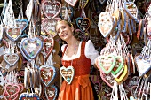 Woman in dirndl by stall selling Lebkuchen hearts (Oktoberfest)