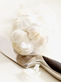 Garlic bulbs in net on kitchen knife