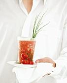 Person serving Spicy Tomato Shot (tomato and orange drink)