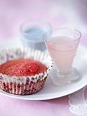 Red cupcake with blue chocolate sauce and liqueur