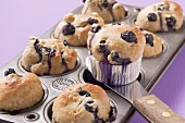 Taking blueberry muffins out of muffin tin