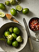 Still life with limes, green physalis and tomato salsa