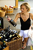 Blond woman buying wine at a market