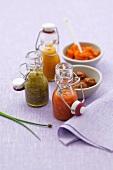 Drei Chilisaucen in Fläschen, Hummerpaste und marinierte Muscheln