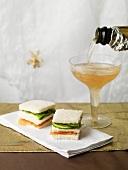 Lachs-Gurkensandwich, ein Glas Champagner einschenken