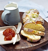 Bread plait with apricot jam and jug of milk
