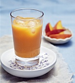 Peach and carrot juice with ice cubes