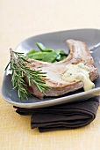 Pork chop with mustard sauce, rosemary and mangetout