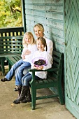 Mother and daughters on a bench outside a forest cabin