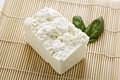A piece of Greek sheep's cheese with two basil leaves