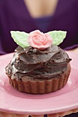 Small cake with chocolate cream and marzipan rose