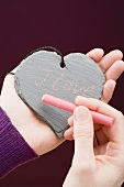 Hand writing I love you in chalk on a slate heart